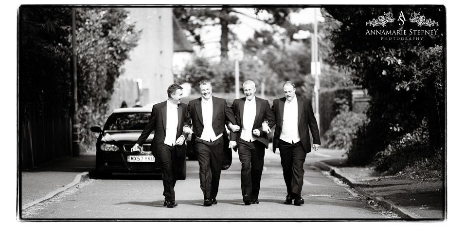 Creative shot of groomsmen walking down the road