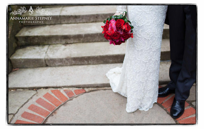 Creative shot of bride and groom together in front of some steps, bride is holding a bright red bouquet ~ Burgh House Wedding Photographer Annamarie Stepney