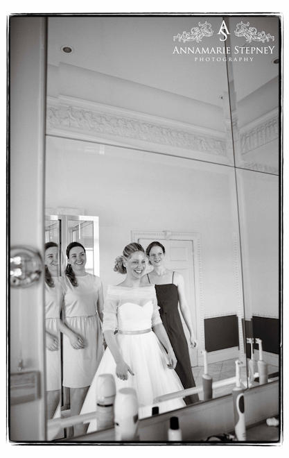 bride with her bridesmaids looking into the mirror ready for her big wedding day